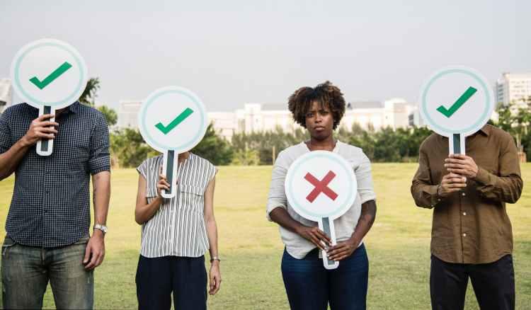 four people holding signage